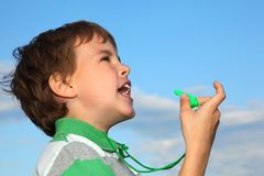 Boy, against blue sky, plays with whistle. The small beautiful boy, against the blue sky, plays with a green whistle. Profile side Royalty Free Stock Images