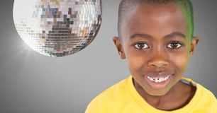 Boy against grey background with disco party ball. Digital composite of Boy against grey background with disco party ball Royalty Free Stock Photo