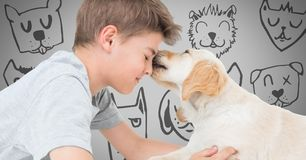 Boy against grey background with friendly dog licking his face and dog faces Royalty Free Stock Photos