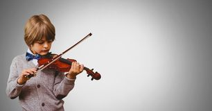Boy against grey background playing violin Royalty Free Stock Image