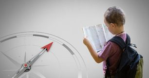 Boy against grey background reading map information and compass. Digital composite of Boy against grey background reading map information and compass Royalty Free Stock Images
