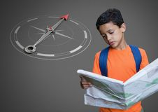Boy against grey background reading map information and orienteering and compass. Digital composite of Boy against grey background reading map information and Royalty Free Stock Image