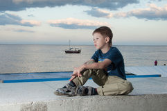 Boy against the sea with the ship Stock Photos