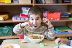 A boy at the age of 5 years eating gruel in the kindergarten. stock photos