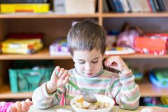 A boy at the age of 5 years eating soup in the kindergarten. stock photos