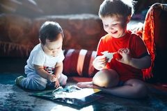 A boy aged three and a girl aged one are playing with book and cards laughing stock photo