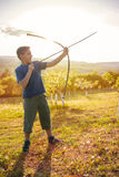 Boy aiming home-made wooden bow outdoors Royalty Free Stock Images