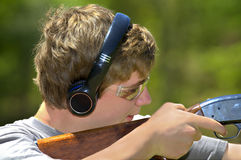 Boy Aiming Shotgun. A young teenager learning to shoot targets with a shotgun stock photos
