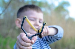 Boy Aiming Sling Shot at Camera Stock Image