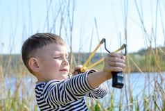 Boy Aiming Sling Shot Outdoors by Lake Royalty Free Stock Image