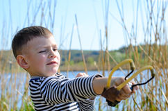 Boy Aiming Sling Shot Outdoors by Lake Royalty Free Stock Photography