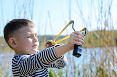Boy Aiming Sling Shot Outdoors by Lake Stock Images