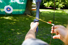 Boy aiming target with bow. Germany,Mecklenburg-Western Pomerania,boy aiming target with bow and arrow, focus on the hands Royalty Free Stock Image