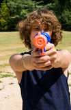Boy aiming water gun at you Stock Photos