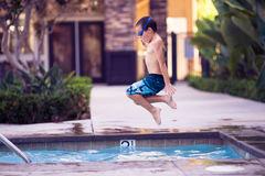 Boy in the air, jumping in a pool Royalty Free Stock Image