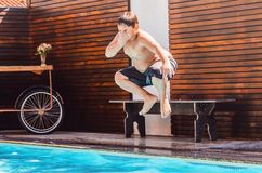 Boy on the air jumping into the swimming pool. Summer holidays Stock Photo