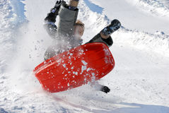 Boy in the Air While Sledding Downhill. Boy in the air while sledding fast down the hill with snow background Royalty Free Stock Image
