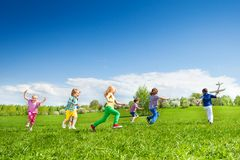 Boy with airplane toy and kids row running after Stock Photo