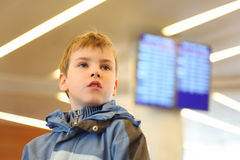 Boy in airport looking into distance Stock Photo