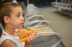 Boy at the airport. Young boy eating pizza while waiting for his flight Royalty Free Stock Photography