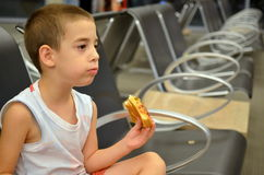 Boy at the airport. Young boy eating pizza while waiting for his flight Stock Photos