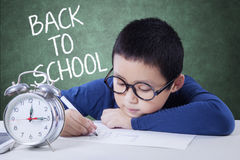 Boy with alarm clock drawing in class Stock Photo