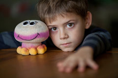 Boy with Alien Toy. Boy with a toy at the table Stock Photos