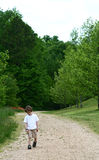 A boy alone. A boy walking alone on a trail in the wilderness Stock Photo