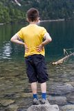 Boy Alone by Lake. A young boy stands alone with hands on hips at the shore of a lake, thinking and dreaming Royalty Free Stock Photos