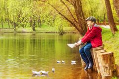 Boy alone near pond playing with  paper boats Royalty Free Stock Photo