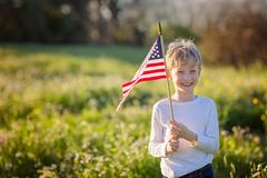 Boy with american flag. Young boy holding american flag celebrating 4th of july, independence day, or memorial day in the park, copy space on left Stock Photo