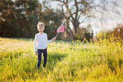 Boy with american flag. Young boy holding american flag celebrating 4th of july, independence day, or memorial day in the park, copy space on right Stock Images
