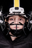 Boy american football player in helmet looking at camera. Close-up view of boy american football player in helmet looking at camera Royalty Free Stock Photos