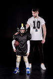 Boy american football player standing with ball near coach. Full length view of boy american football player standing with ball near coach stock images