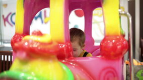 Boy in amusement train. Little boy swinging in colorful amusement train on indoor playground stock video