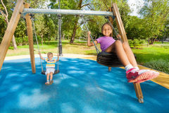 Boy And Girl Singing On Swings Royalty Free Stock Images