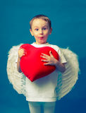 Boy angel heart valentine. Angel in a white boy holding a big heart Royalty Free Stock Image