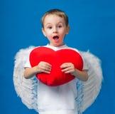 Boy angel heart valentine. Angel in a white boy holding a big heart Stock Photos