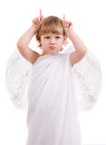 Boy angel shows horns. Raspberries boy angel with wings, horns shows hands and teasing Royalty Free Stock Photos