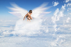 Boy with Angel Wings flying around in the sky. Above the clouds Royalty Free Stock Images