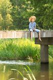 Boy during angling with rod on bridge. At a straw hat Royalty Free Stock Photos