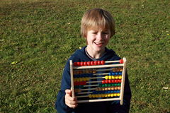 Boy angry from counting. Little boy that is angry from counting on a colorful abacus stock image