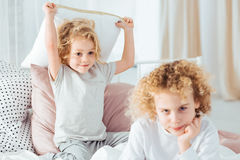 Boy annoying his older brother. Cute boy with pillow annoying his older brother royalty free stock photo
