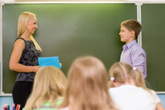 Boy answers questions of teachers near a school board Royalty Free Stock Photos