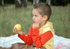 Boy with an apple Stock Images