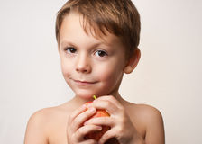 Boy with an apple. Young child holding an apple on a white background Royalty Free Stock Images