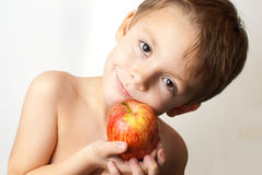 Boy with an apple. Young child holding an apple on a white background Stock Image