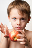 Boy with an apple. Young child holding an apple on a white background Stock Photos