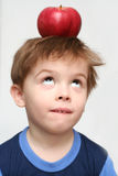 The boy and an apple. The boy at which on a head is a red apple Stock Photo