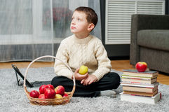 Boy with apples and books  at home Stock Photography